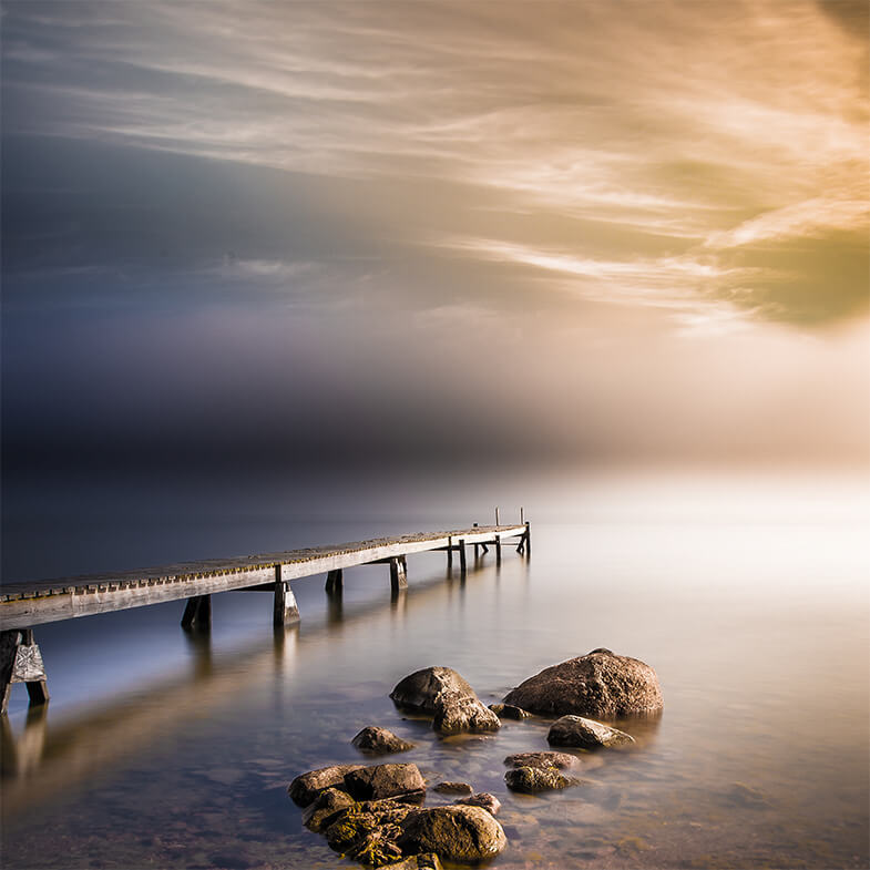 Wooden pier stretching out over a calm sea. Cover photo for MPA network design and management. Photo: Shutterstock.