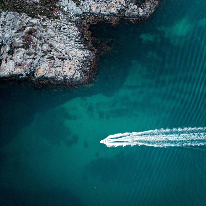 Drone photo of a boat speeding across transparent water in Sweden